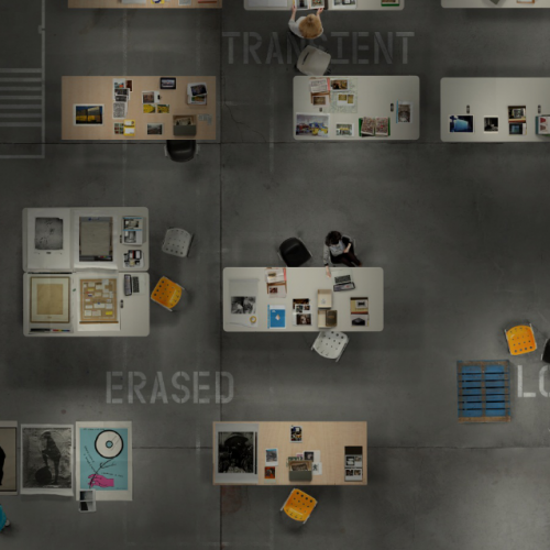 "Bird's eye view of a concrete floor with archival-material covered tables strewn across it. Words such as ""transient"" and ""erased"" are stenciled on the ground. This is a screenshot of the Gallery of Lost Art website."