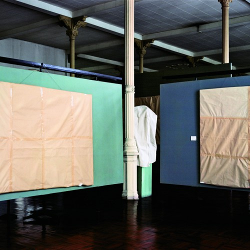 Two false walls in a dim room are painted green and blue. Hanging on each wall is a large rectangle covered with brown paper and packaging tape. Artwork credit: Edi Hirose, Trinity, 2010, ink-jet print on cotton, 43¼ by 54 inches. Courtesy Galería Lucía de la Puente, Lima.