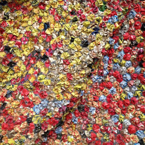 A patchwork of red, gold, blue, and silver florets made from discarded aluminum cans. Artwork by El Anatsui.