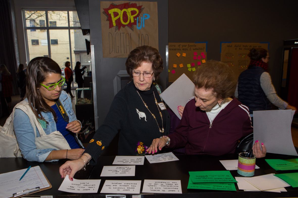 A woman watches as two older women arrange the large white index cards on the counter. One woman wears a black sweater with a ghost near the collar and pumpkins around the opening of her sleeve. She has short brown hair and thin, rectangular glasses. The woman next to her has short lighter brown hair and hot pink fingernails. She wears a burgundy tracksuit jacket with two white stripes down the sleeve.