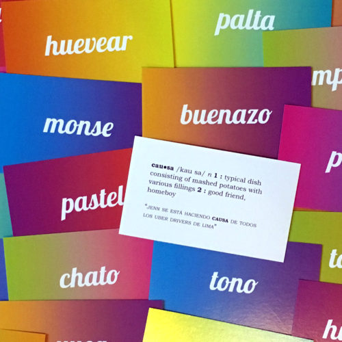 "Colorful flashcards bearing words such as ""pastel,"" ""tono,"" and ""buenazo"" are arranged in a pile. In the center, one of the cards is turned face-up, displaying two possible definitions of the word ""causa"": 1.) ""a typical dish consisting of mashed potatoes with various fillings,"" or 2.) ""a good friend, homeboy"""