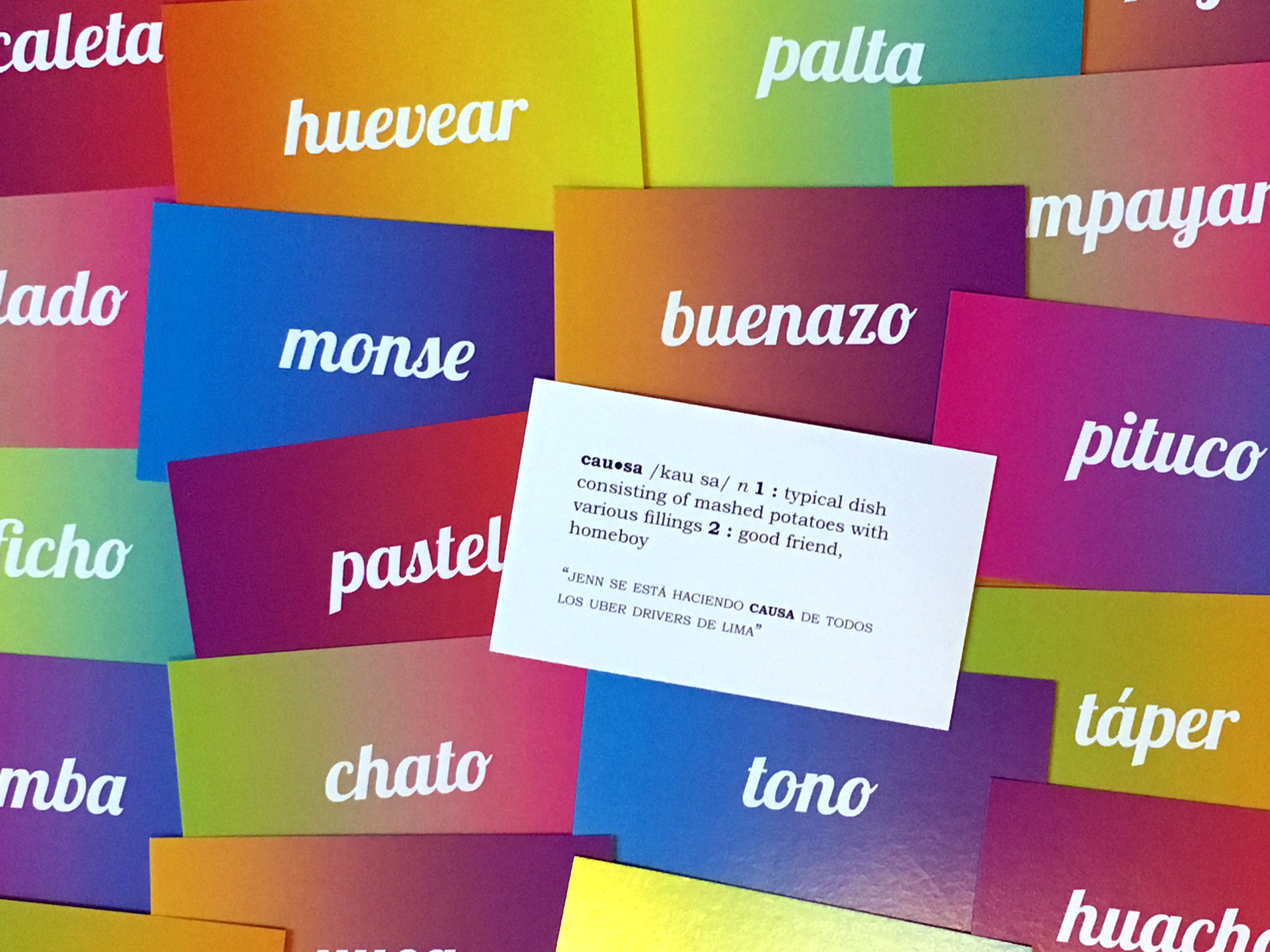 """Colorful flashcards bearing words such as """"pastel,"""" """"tono,"""" and """"buenazo"""" are arranged in a pile. In the center, one of the cards is turned face-up, displaying two possible definitions of the word """"causa"""": 1.) """"a typical dish consisting of mashed potatoes with various fillings,"""" or 2.) """"a good friend, homeboy"""""""