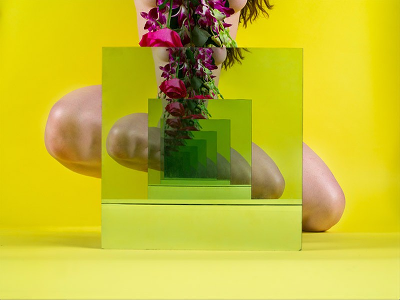 This photograph is by artist Sarah Meyohas. It depicts a recursive images of a woman's bare legs, her pelvis in the middle obscured by a mirror. Above the mirror we glimpse a little bit of bold pink flowers. The background is yellow.