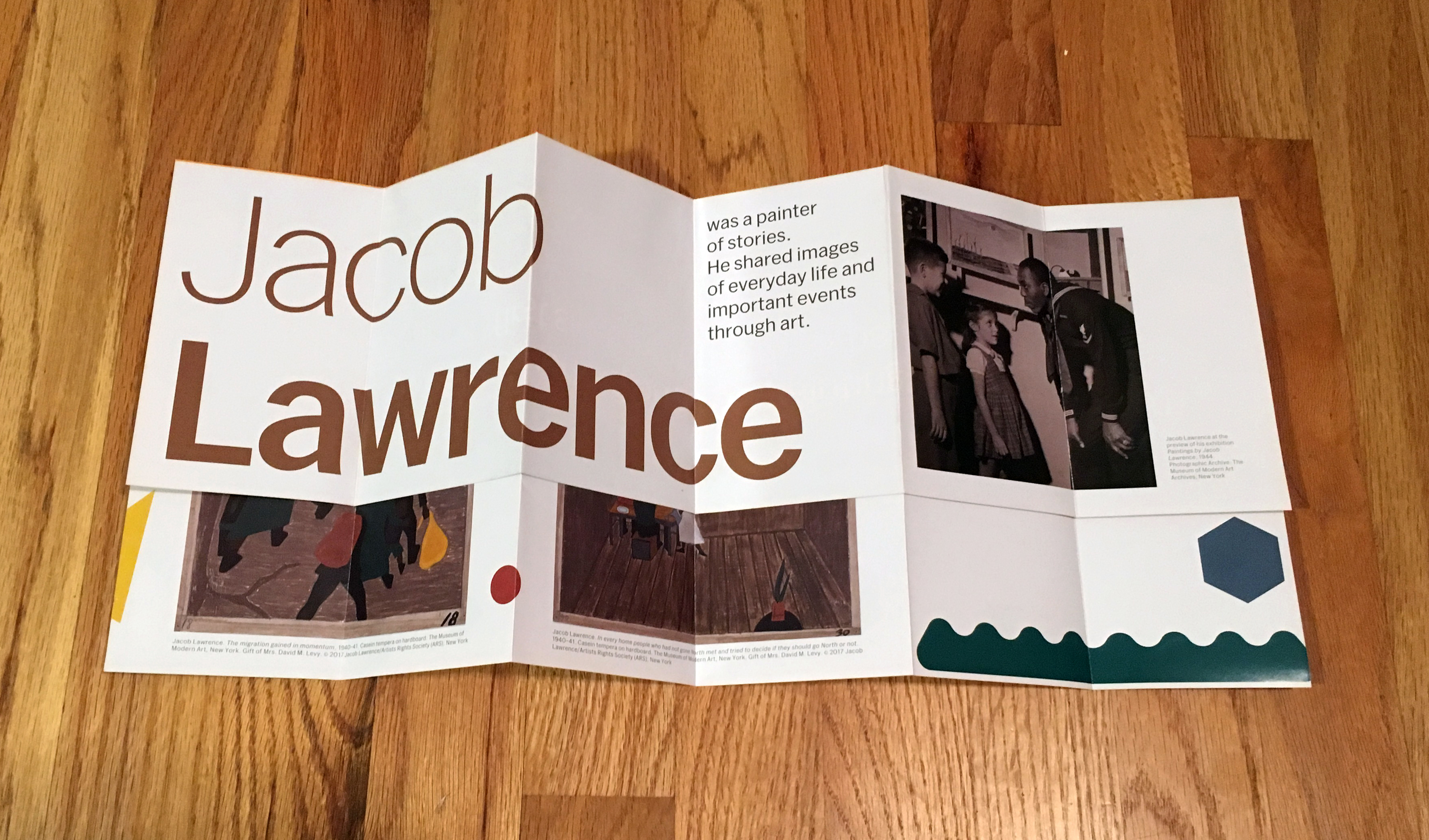 "A pamphlet unfolded halfway reads ""Jacob Lawrence was a painter of stories."""