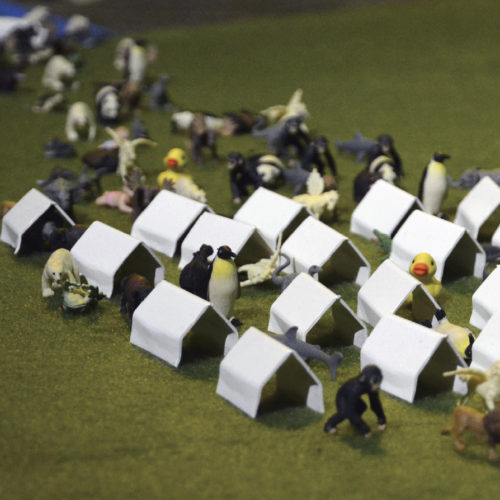 Dozens of tiny tents and assorted animal figurines are assembled in a caravan, marching along green grass