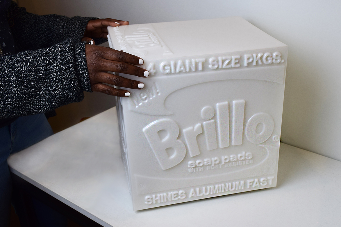 Two hands touch a white 3-d printed replica of Andy Warhol's Brillo Box sculpture