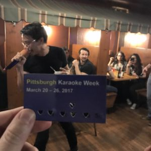 A Karaoke week punchcard with a man singing in the background