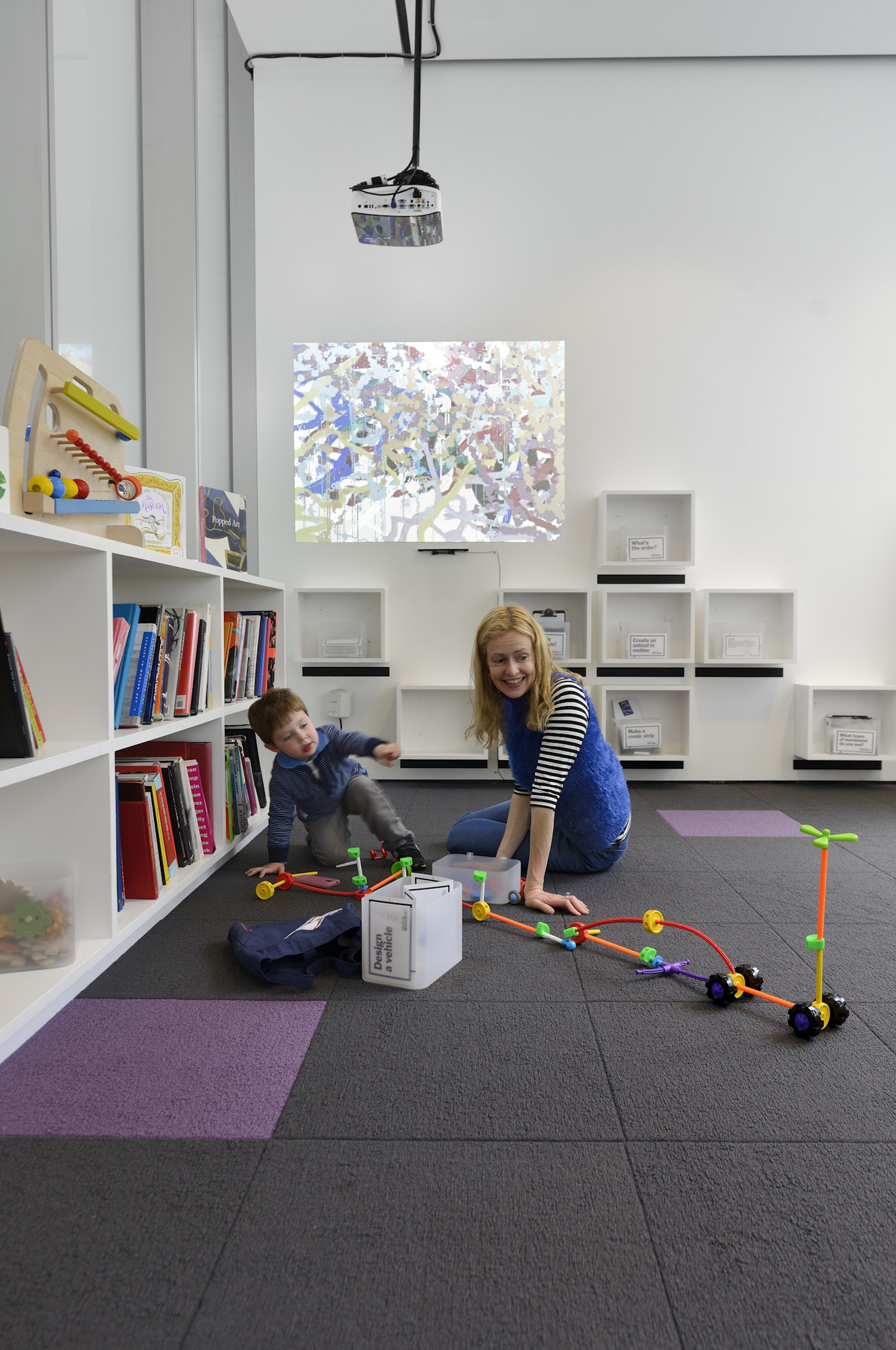 A child and a woman play with tinker toys