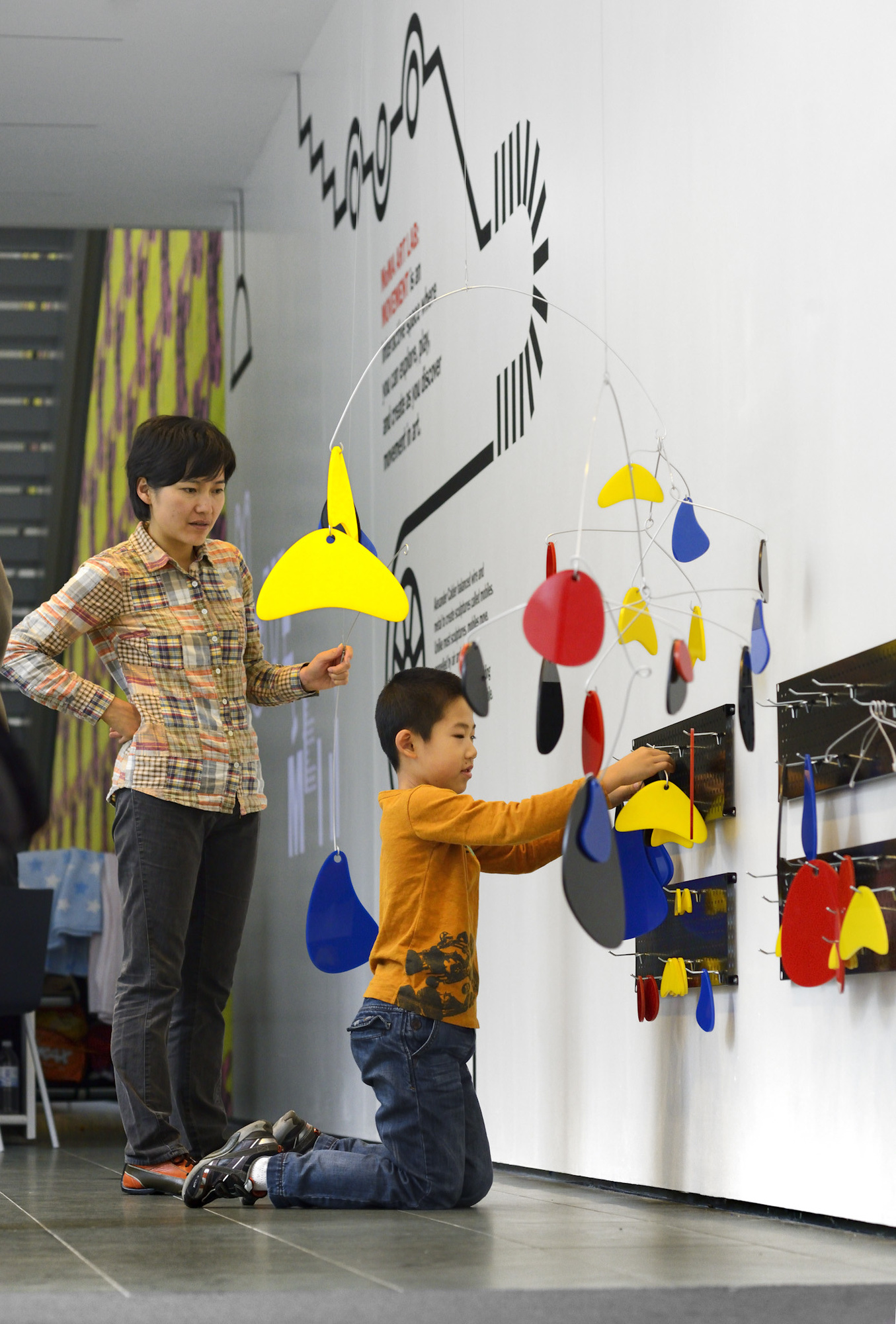 A kid adds shapes to an Alexander Calder-inspired mobile