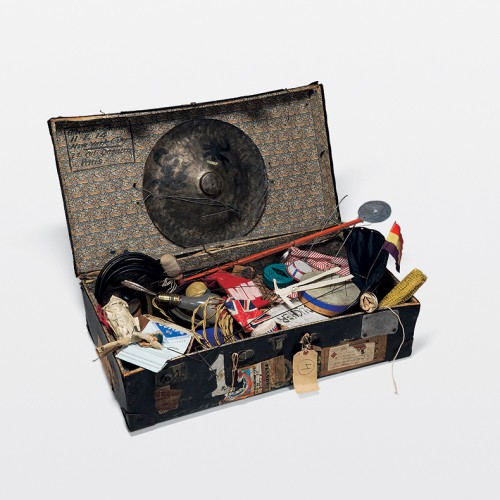 An open suitcase full of assorted objects, including a light bulb, miniature British flag, and cymbal. Part of Alexander Calder's Circus, Whitney Museum of American Art.