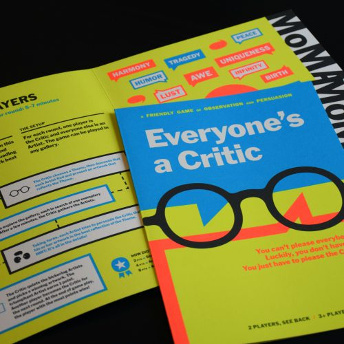 Two Everyone's a Critic game pamphlets lie on a black surface